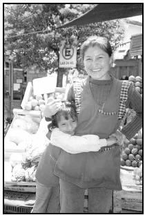 An Argentine fruit and vegetable vendor and her daughter greet customers at a market. Cory Langley
