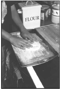 To make Damper (European Style), shape dough into a large flat circle on a greased and floured baking sheet. EPD Photos