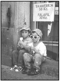 Two Czech children enjoy ice cream, seated on the threshold of a shop advertising two Middle Eastern favorites—shawerma (grilled, skewered meat) and falafil (deep-fried chickpea balls), with prices quoted in Czech currency, the koruny (Kc). Cory Langley