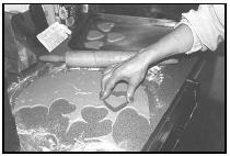 After rolling out the dough, cut the lebkuchen into shapes such as hearts or teddy bears. If the cookies are to be hung by a ribbon, pierce one or two holes in the dough near the top of the cookie. EPD Photos