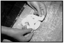 Making soft pretzels. Twist the ropes into pretzel shapes and place them on a greased cookie sheet. EPD Photos