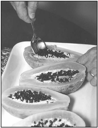 Arrange the peeled papaya halves, cut side up, in a baking dish. Scoop out the seeds before baking the papaya dessert. EPD Photos