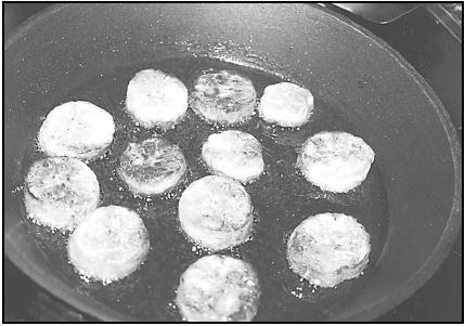 Dodo (fried plantain slices) sizzle in the frying pan. Fried plantains are often served for breakfast or as a snack. EPD Photos