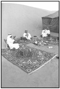 Saudis arrange ornate rugs around a central fire when outdoors, as these men are, or around dishes of food being served when indoors. Diners sit on the rugs and share food and conversation. EPD Photos/Brown W. Cannon III