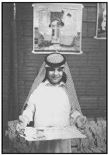 A young man presents coffee on a tray to a guest. The Saudis take pride in their hospitality, and it is considered rude to refuse a host's offer of refreshments. EPD Photos/Brown W. Cannon III