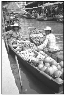 Thai fruit and vegetable vendors often sell their wares from long boats, moving from dock to dock to serve their customers. Cory Langley