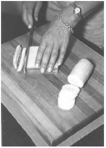 The crusts from thin-sliced white bread are trimmed to make cucumber sandwiches to serve at teatime. The cucumber is peeled and sliced thinly. EPD Photos