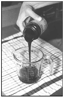 Molasses Water combines thick, sweet molasses, shown here being poured into a measuring cup, with lemon juice and water. Molasses Water is similar to lemonade, sweetened with the distinctive molasses flavor. EPD Photos