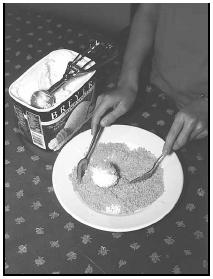 Using two forks, gently roll the scoop of ice cream around in the corn flake crumbs until the entire surface is covered with a crunch coating. EPD Photos